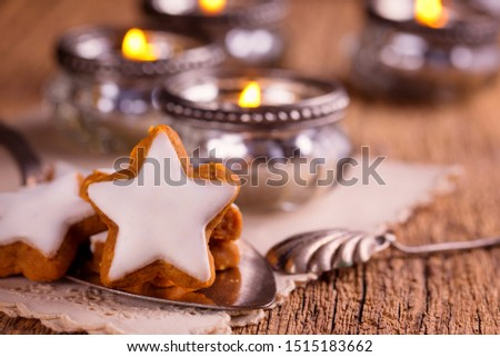 Close up of Christmas cookies, cinnamon rolls and vintage candles on rustic wooden table  -  Festive Vintage Christmas table #1515183662