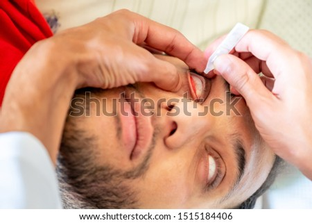 Doctor giving his patient eye drops in his eyes #1515184406