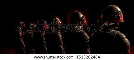 Special forces soldiers in black uniform and helmets on black background. The soldiers illuminated by red light. Middle shot. View from the back. Military, police, army concept. Wide picture