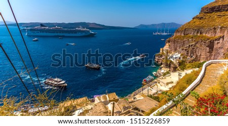 A view beside the cable car route leading down from the town of Fira to the port below in summertime #1515226859