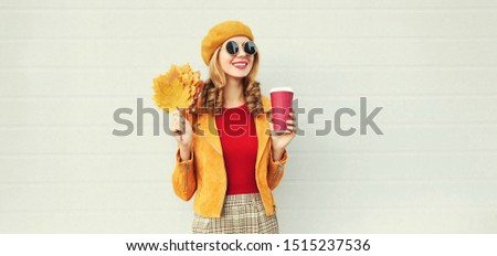 Portrait stylish happy smiling woman with yellow maple leaves, coffee cup in french beret posing over gray wall background #1515237536