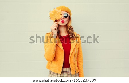 Autumn portrait woman holding in her hands yellow maple leaves covering her eye, girl blowing red lips sending sweet air kiss over gray wall background #1515237539
