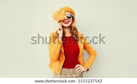 Autumn portrait happy smiling woman holding in her hands yellow maple leaves covering her eye over gray wall background #1515237542