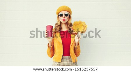 Autumn portrait woman with yellow maple leaves, coffee cup blowing red lips sending sweet air kiss over gray wall background #1515237557