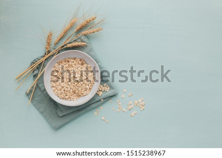 Bowl of dry oat flakes with ears of wheat on light blue background. Cooking oats porridge concept. flat lay #1515238967