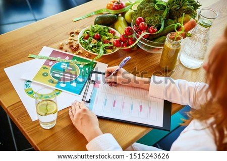 Woman dietitian in medical uniform with tape measure working on a diet plan sitting with different healthy food ingredients in the green office on background. Weight loss and right nutrition concept #1515243626