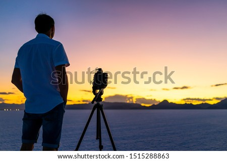 Bonneville Salt Flats near Salt Lake City, Utah at colorful twilight with purple sky and man standing by tripod with camera doing time lapse photography #1515288863