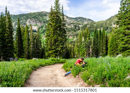 Albion Basin, Utah summer with man sitting taking pictures of landscape view by dirt road trail in Wasatch mountains to Cecret Lake