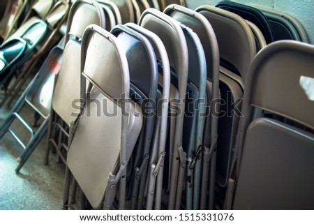 Stacks and Rows of Metal Steel Iron Collapsible Fold Up Folding Chairs o Different Colors leaning up against a Brick Cinder Block Wall in a Storage Room #1515331076