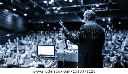 Speaker giving a talk on corporate business conference. Unrecognizable people in audience at conference hall. Business and Entrepreneurship event. Black and white, blue toned image. #1515371126