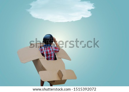 Little boy in a cardboard airplane. Child is pretending to be a pilot. Travel, freedom and imagination concept #1515392072
