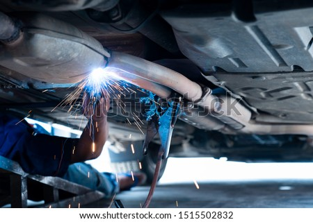 The hand of a mechanic or welder is fixing a car exhaust system by welding the exhaust pipe. Sparks of automobile exhaust pipe welding. Auto services. Selective focus. Copy space. #1515502832