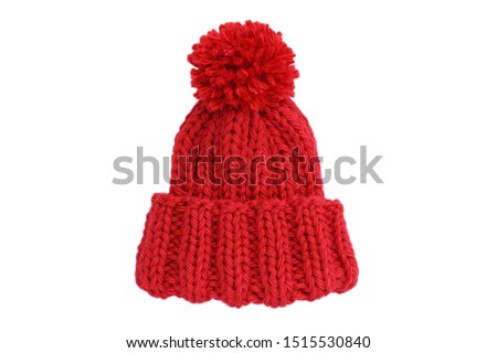 Small red knitted bobble hat isolated on a white background. Handmade woolly hat with pompom. Closeup. Copy space Royalty-Free Stock Photo #1515530840