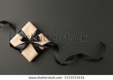 Craft gift box on a dark background, decorated with a textured bow and feathers, creating a romantic luxury atmosphere. For birthday, anniversary presents, gift post cards. #1515553616