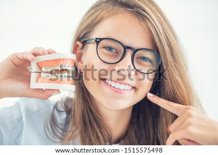 Model of a dental braces in the hand of a young girl with aligned teeth after the process of using a dental brace. #1515575498