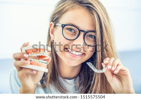 Dental invisible braces or silicone trainer in the hands of a young smiling girl. Orthodontic concept - Invisalign. #1515575504