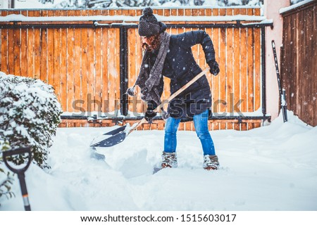 woman with shovel cleaning snow. Winter shoveling. Removing snow after blizzard #1515603017
