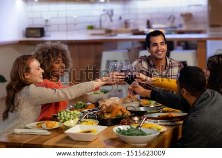 Side view of a group of young adult multi-ethnic male and female friends sitting at a table at home set for Thanksgiving dinner making a toast with glasses of red wine #1515623009