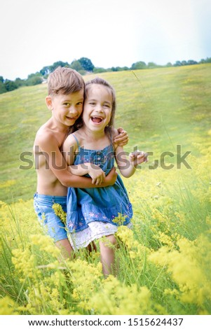happy kids boy and girl play in field on meadow in flowers in nature #1515624437