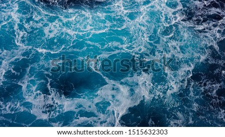 background pacific ocean during a typhoon, bright blue color of a sea splashing wave, texture of sea foam. abstraction of ripped water waves in the ocean in a storm sunlight. turbulent ocean #1515632303