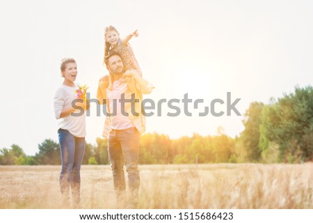 Happy family walking in wheat field with yellow lens flare in background #1515686423