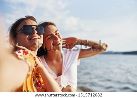 Selfie of two smiling girls outdoors that have a good weekend together at sunny day against the lake. #1515712082