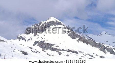 View of the snow covered mountain with visible rocky parts above a glacier ski resort ski resort in spring #1515718193