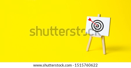 Sign stand with an arrow in the target on a yellow background. Hit exactly on center. Tactics of advertising targeting. advertise campaigns. Goal Achievement and Purposefulness #1515760622