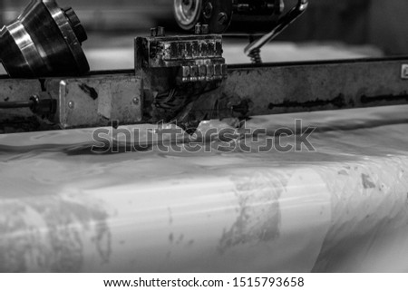 Black and white close up shot of an industrial plastic slicing or cutting machine in heavy duty industrial factory producing mass packaging for outdoor and industry use for the masses. eco friendly  #1515793658
