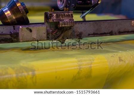 Close up shot of an industrial plastic slicing or cutting machine in heavy duty industrial factory producing mass packaging for outdoor and industry use for the masses. contributing to pollution  #1515793661