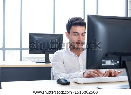 Successful Caucasian smart employee looking at computer in alone office. Businessman working in small startup business. He working on online communication technology. Startup entrepreneur concept.   #1515802508
