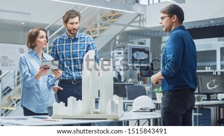 In Architectural Bureau: Team of Architects and Engineers Working on a Building Complex Prototype Project, Using City Model and Computers Running 3D CAD Software. Residential or Business District #1515843491