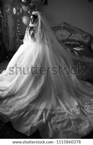 Kind of bride from the back, romantic atmosphere of the bride's morning. Beautiful bride in wedding dress. Bride in a home. Bride's morning. Bride morning preparation. Black and white #1515860378