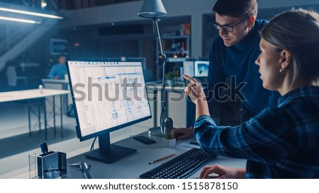 Engineer Working on Desktop Computer, Screen Showing CAD Software with Technical Blueprints, Her Male Project Manager Explains Job Specifics. Industrial Design Engineering Facility Office Royalty-Free Stock Photo #1515878150
