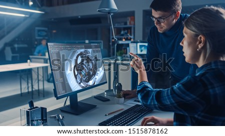Engineer Working on Desktop Computer, Screen Showing CAD Software with Engine 3D Model, Her Male Project Manager Explains Job Specifics. Industrial Design Engineering Facility Office #1515878162