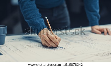 In the Dark Industrial Design Engineering Facility: Male Engineer Works with Blueprints Laying on a Table, Uses Pencil, Ruler and Digital Tablet. On Desktop Multiple Drawings. Focus on Hands #1515878342