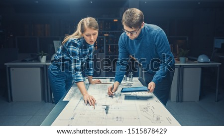 In the Dark Industrial Design Engineering Facility Male and Female Engineers Talk and Work on a Blueprints Using Conference Table. On the Desktop Drawings, Drafts and Electric Engine Components, Parts #1515878429