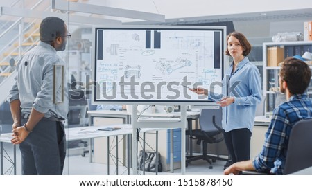 In Industrial Design Facility Team of Engineers and Technicians have a Meeting, Female Specialist Leads Briefing, Talks and Draws on Digital Interactive Whiteboard with Car Prototype Concepts #1515878450
