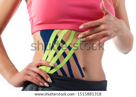 Woman shows kinesio tapes taped to her belly. Bright medical tape on the abdomen of a girl #1515881318
