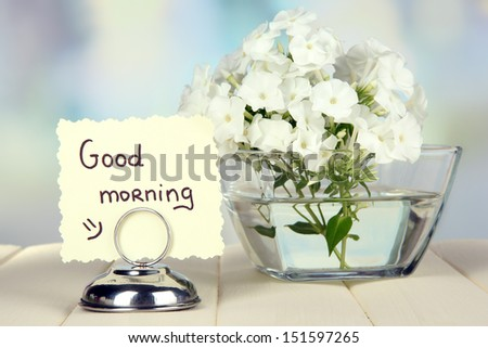Beautiful bouquet of phlox in bowl on table on light background