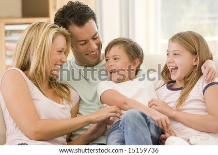 Family sitting in living room smiling #15159736