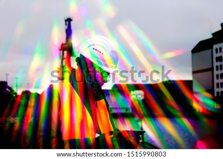 worker with helmet and smart phone and colorful stripes of light #1515990803