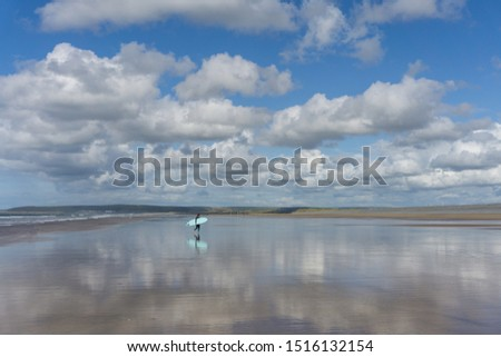 Surfer on a reflective Westward Ho Beach in Devon , England Royalty-Free Stock Photo #1516132154