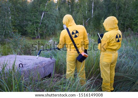 Two dosimetrist  in protective suite and mask with geiger counter measuring radiation level in danger zone #1516149008