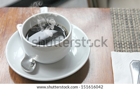 The picture hot Black coffee in a white cup on the table and have smoke coming out.