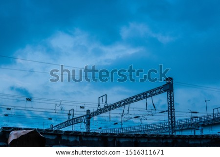 The electric wires spreading under the cloudy evening sky / The electric facility of a train station #1516311671