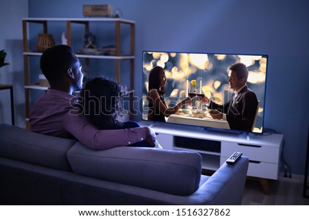Affectionate Young Family Watching TV At Home Royalty-Free Stock Photo #1516327862