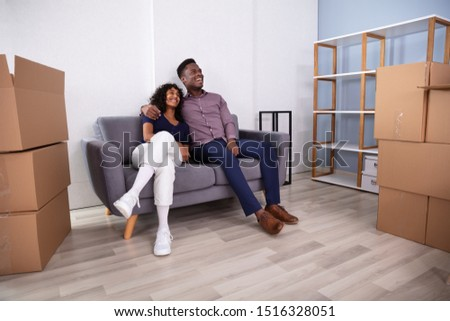 Young Couple Sitting On Couch Inside Their New Home #1516328051