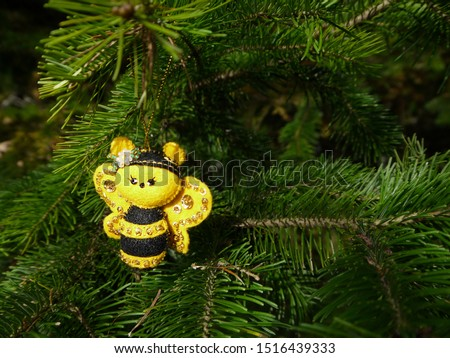 Christmas felt decoration on a spruce branch. Handmade bauble figurines a cute bee. Holiday background with a copy space. Suitable for greeting cards, banners and posters.