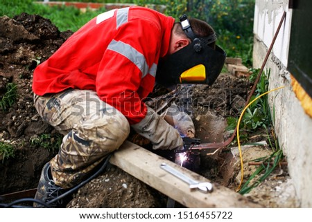 Welder constructing earth grounding system. Man in welding mask performing weld construction. Worker with weld equipment (welding machine, electrode and mask) conducting metal works. Metalworking #1516455722
